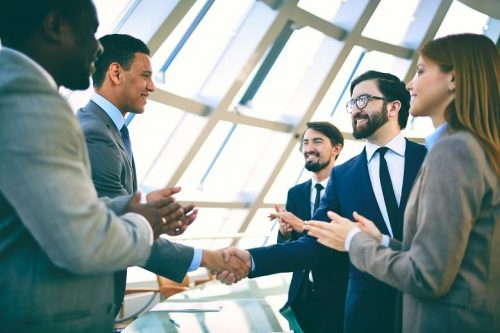 Group of male and female accountants shake hands at a networking event.