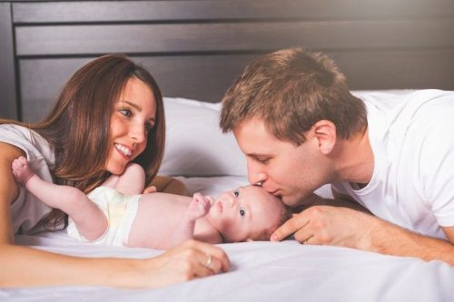 Parents cuddle with their newborn at home.