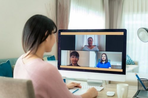 Cyber security professional participates in a virtual meeting on the computer while working from home.