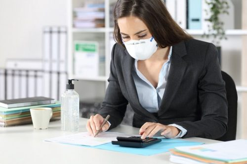 An accounting wears a medical face mask while working at her desk.