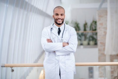A nurse leader folds his arms and smiles.