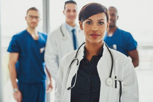 A nurse practitioner stands in front of her team.