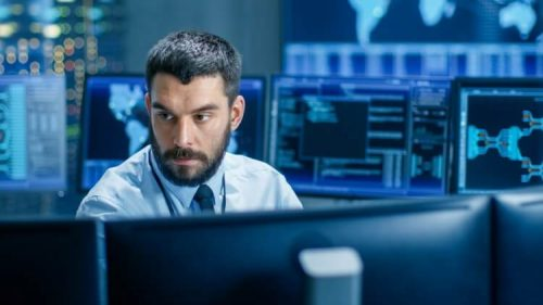 Cyber intelligence analyst in the security control room surrounded by monitors.