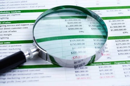 Magnifying glass rests over spreadsheet of accounting information to investigate financial wrongdoing in criminal and civil cases.