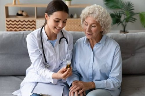 A young female nurse practitioner discusses a medication with an elderly woman.