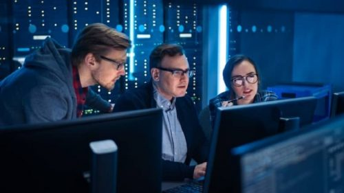 Three cyber security professionals are gathered around a computer monitor to analyze a potential network vulnerability.