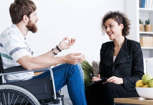 A smiling person holding a notebook and wearing business attire has a conversation with a person who is in a wheelchair and is talking animatedly.