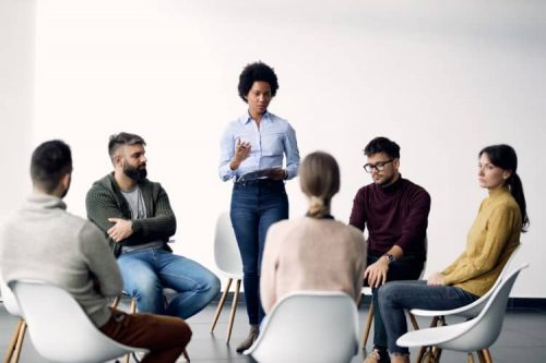 An addiction counselor leads a group therapy meeting.