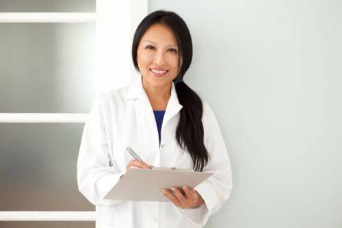 A smiling D.N.P.-prepared nurse writes on a clipboard.