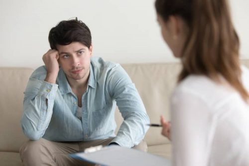 A person with a troubled expression leans forward on a couch listening to a mental health professional.