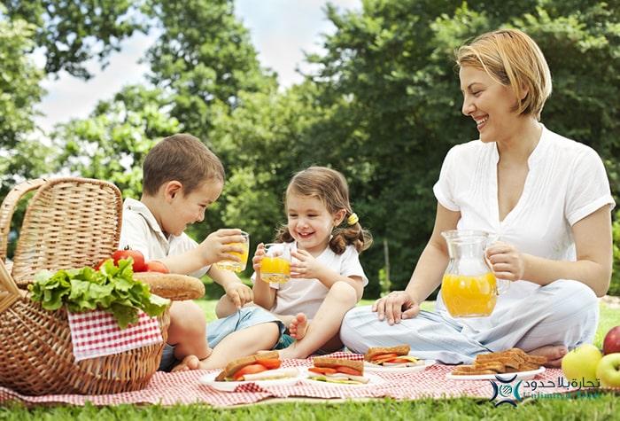 صورة عائلة في نزهة عائلية يتناولون عصائر غير متأكسدة من خلاط كووك