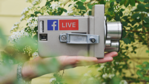 a hand holds a film camera with a Facebook Live sticker on it