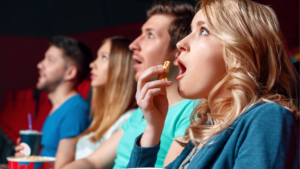a row of people sitting in a movie theatre eating popcorn and looking in awe at a promo video