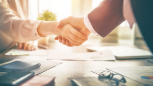 a woman and man dressed in business attire shake hands over paperwork
