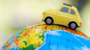 a yellow toy card placed on a globe represents video distribution around the world