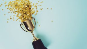 a trophy with confetti to show excitement around the announcement of the 2019 Video in Business Award winners