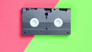 a VHS video tape on a brightly colored background serves as a symbol of B2B video marketing examples