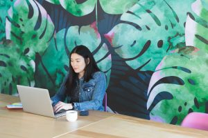 Woman working in an office on her laptop with a leaf mural on the wall behind her