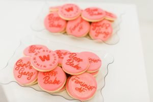 Pink & red custom We Are Women Owned Logo Cookies with some reading