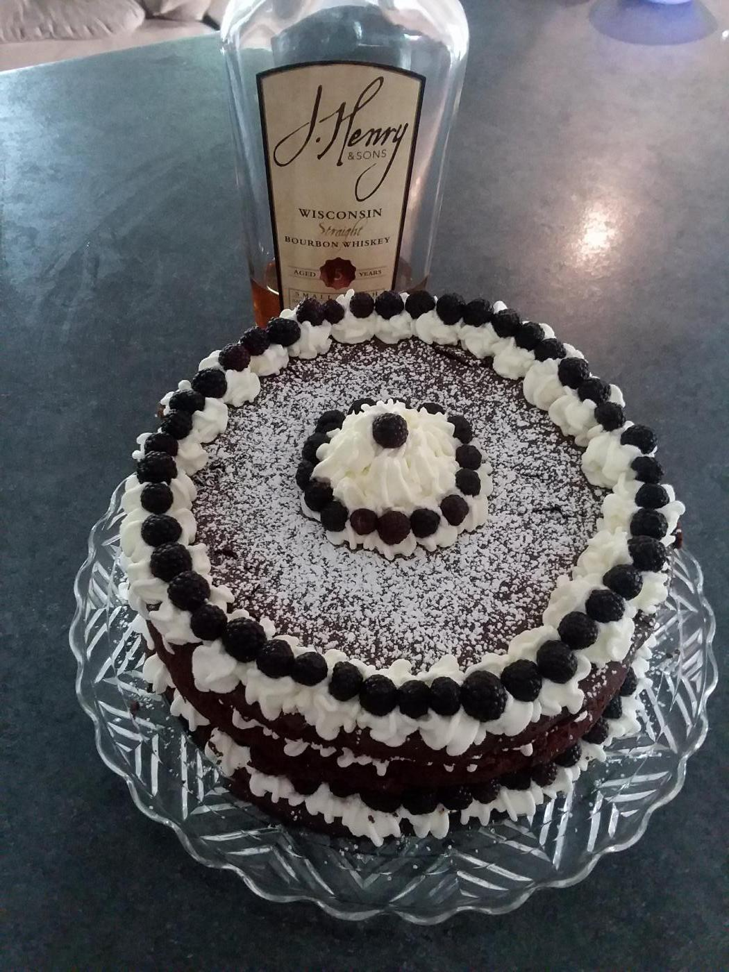 Marie's Good Neighbor Torte is ringed with whipped cream and blackberries and contains J. Henry Bourbon