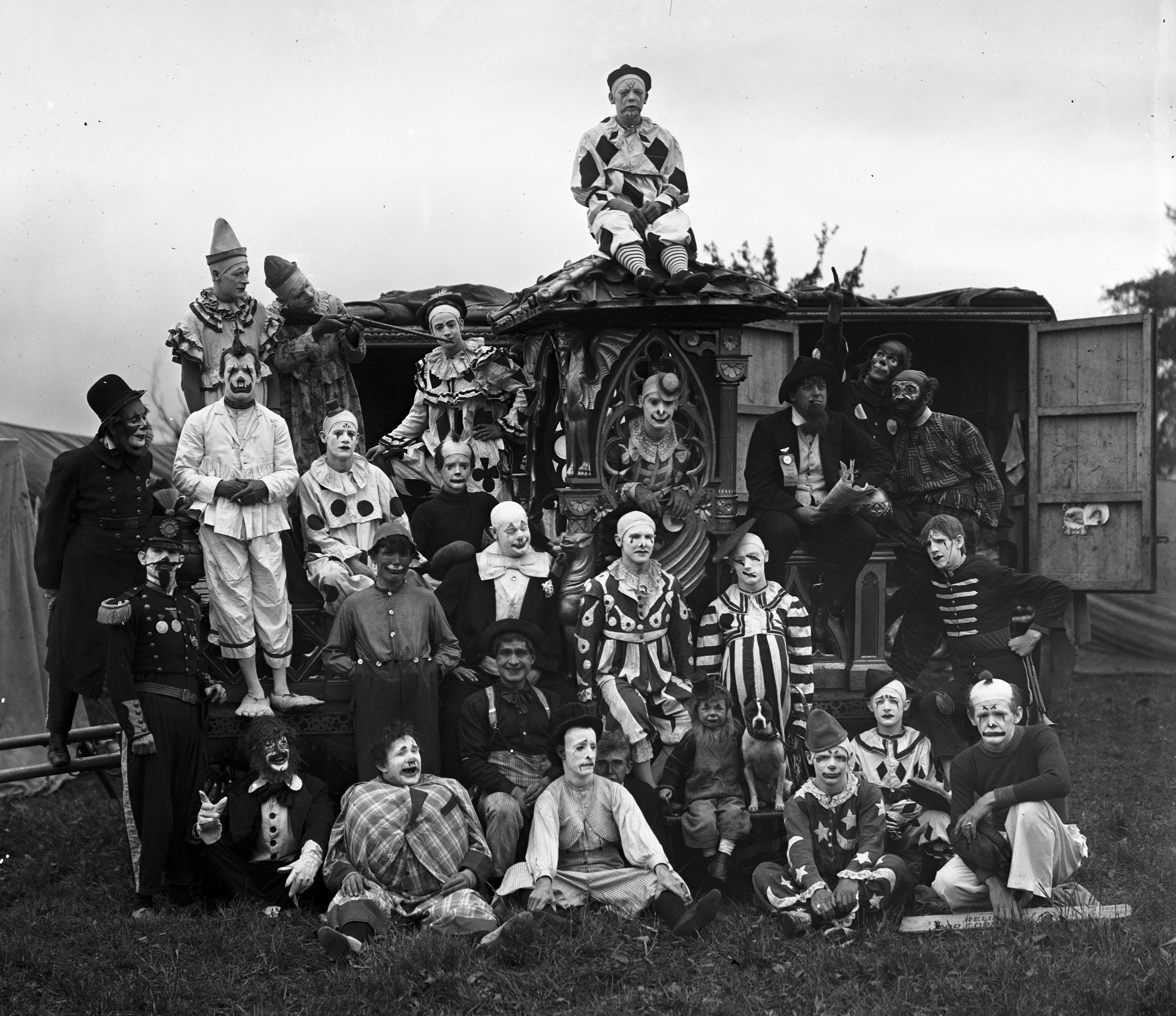 A group of clowns poses together in the early 20th century
