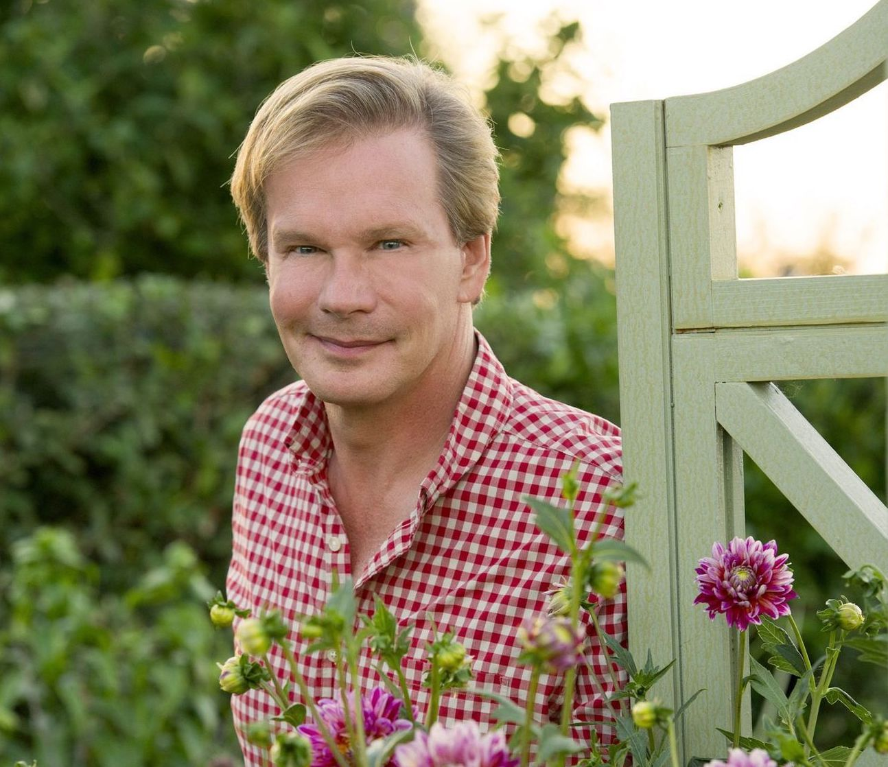 P. Allen Smith smiles behind a trellis and some purple flowers