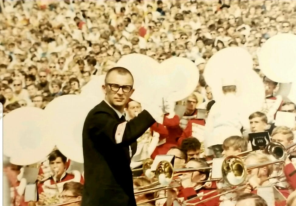 A buzz-cut-sporting Mike Leckrone leads the Badger band at a football game.