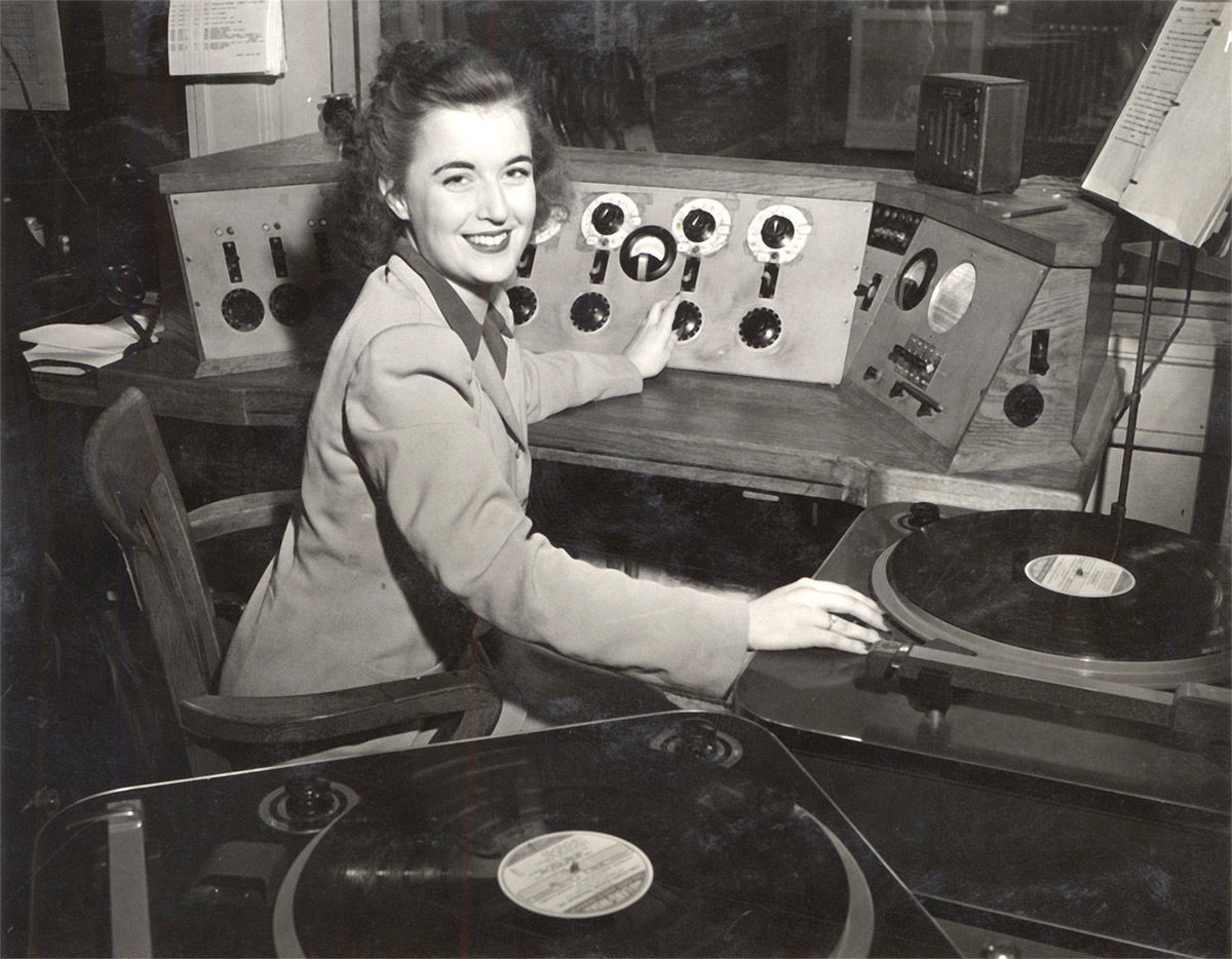 Peg Bolger at the studios in Radio Hall in the 1940s. During World War II radio students and staff, including Program Director Harold McCarty, Harold Engel and other key personnel, left to serve in the Armed Forces. Although women had been on the air since the 1920s, the station trained female students to work as operators and announcers for the first time. Peg Bolger, UW Madison Class of 1942, was one of the students who learned to run the control board in Radio Hall. Bolger also performed in radio dramas as part of the WHA Players. UW-Madison Archives Images: S08156 Dated ca. 1949
