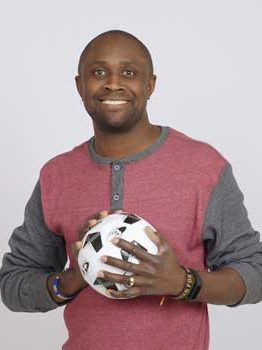 Baptiste Paul, a smiling dark-skinned man with close-cropped hair, holds a soccer ball