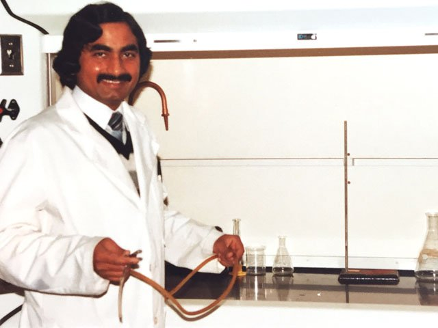 A young Masood Akhtar smiles while working in a lab.
