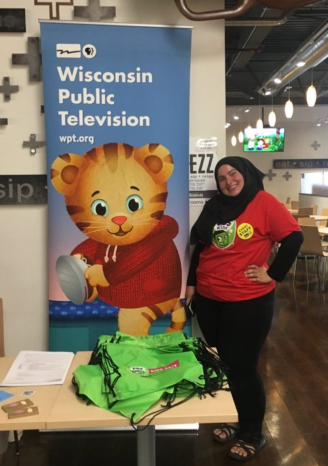 Mouna Algahaithi poses by a Daniel Tiger banner at 2018s Sensory Friendly Time
