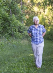 Sister Mary David Walgenbach walks in a wooded area