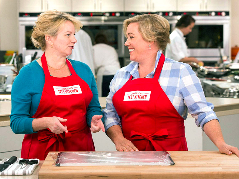 Hosts Bridget Lancaster and Julia Collin Davison discuss a recipe in the ATK kitchen wearing red aprons