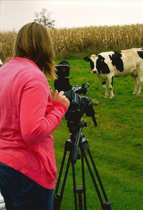 Holly De Ruyter is seen from the back as she films a black and white cow in a field