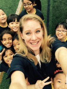 Miranda Paul, a smiling light-skinned woman with long blonde hair, takes a selfie with a group of happy kids