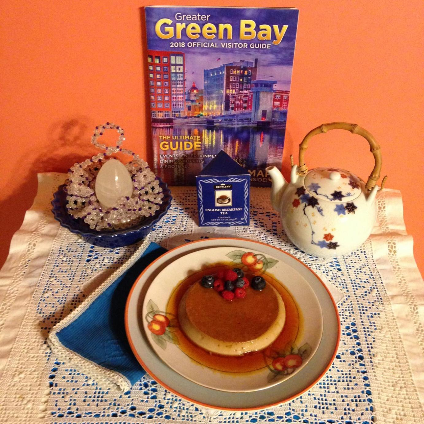 Becky displays her creme caramel with a teapot and a Green Bay visitors' guide