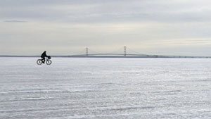 Image of ice with bridge to Mackinac in background