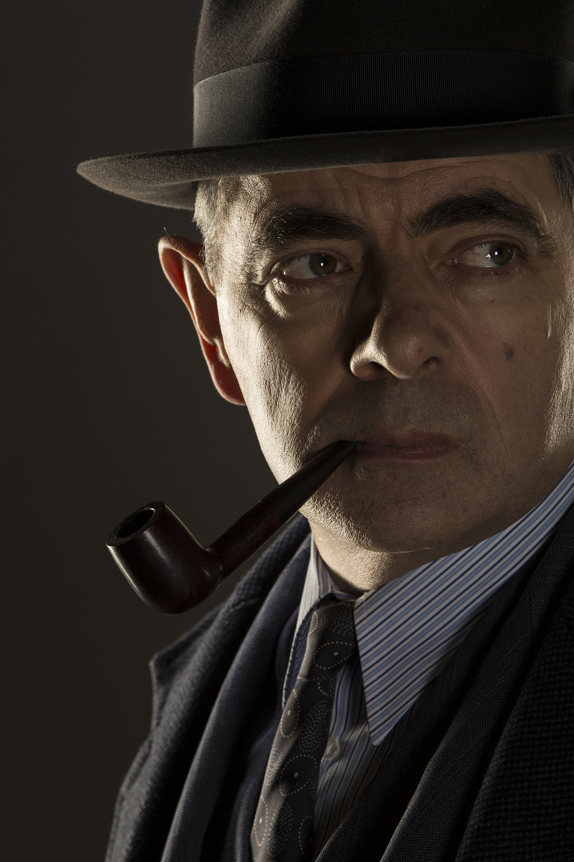 Jules Maigret (Rowan Atkinson) poses with a pipe and fedora.