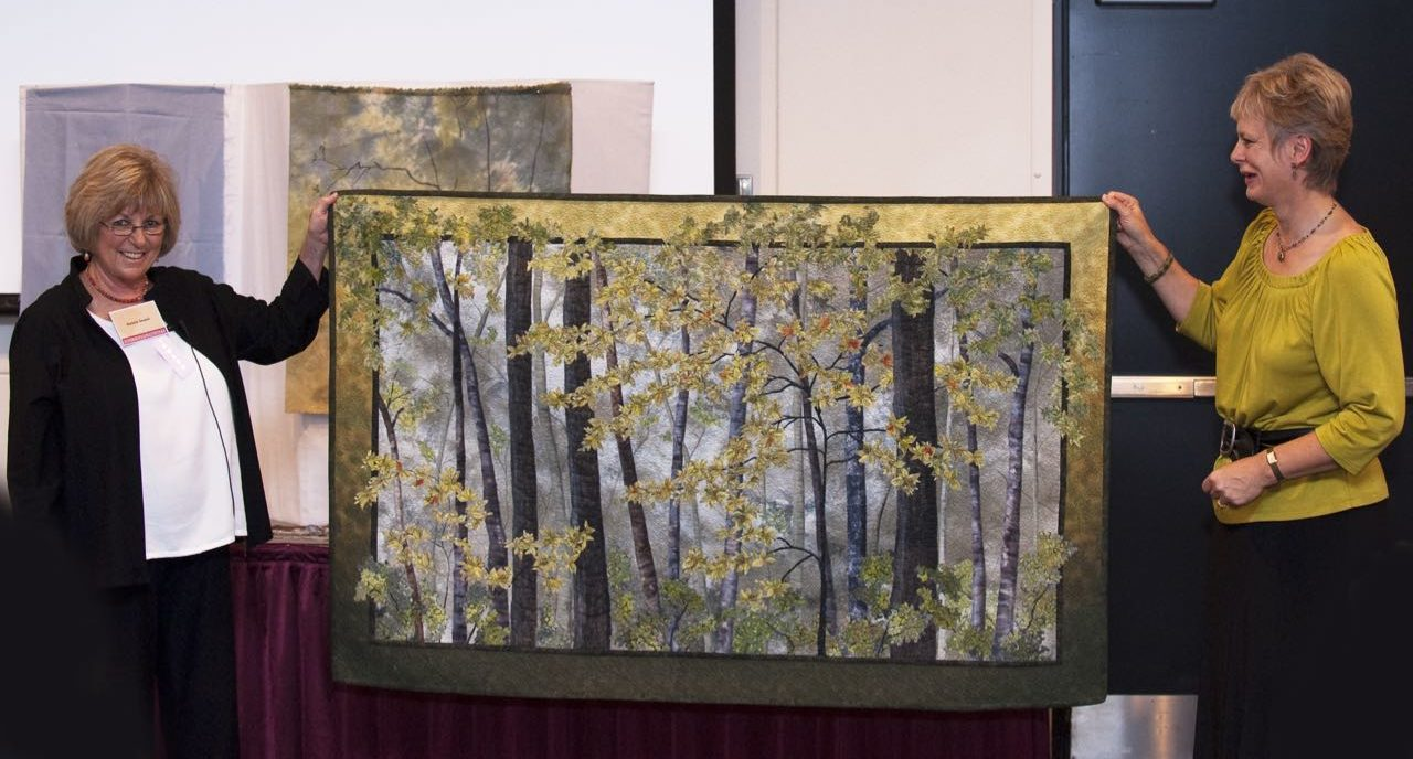 Natalie Sewell and Nancy Zieman display one of their collaborative landscape quilts
