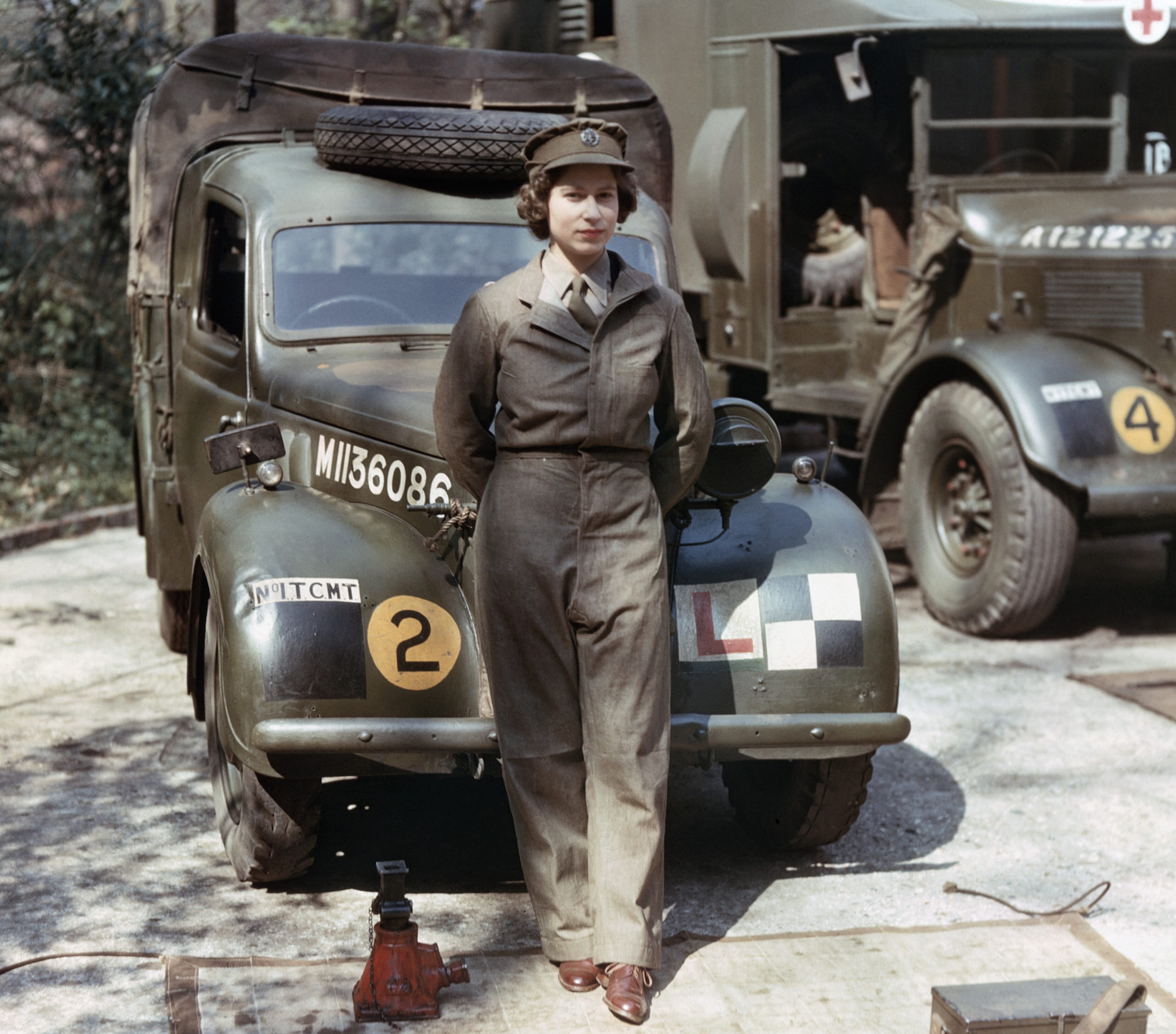 The future Queen Elizabeth II, wearing a military uniform, poses by a WWII medical vehicle.
