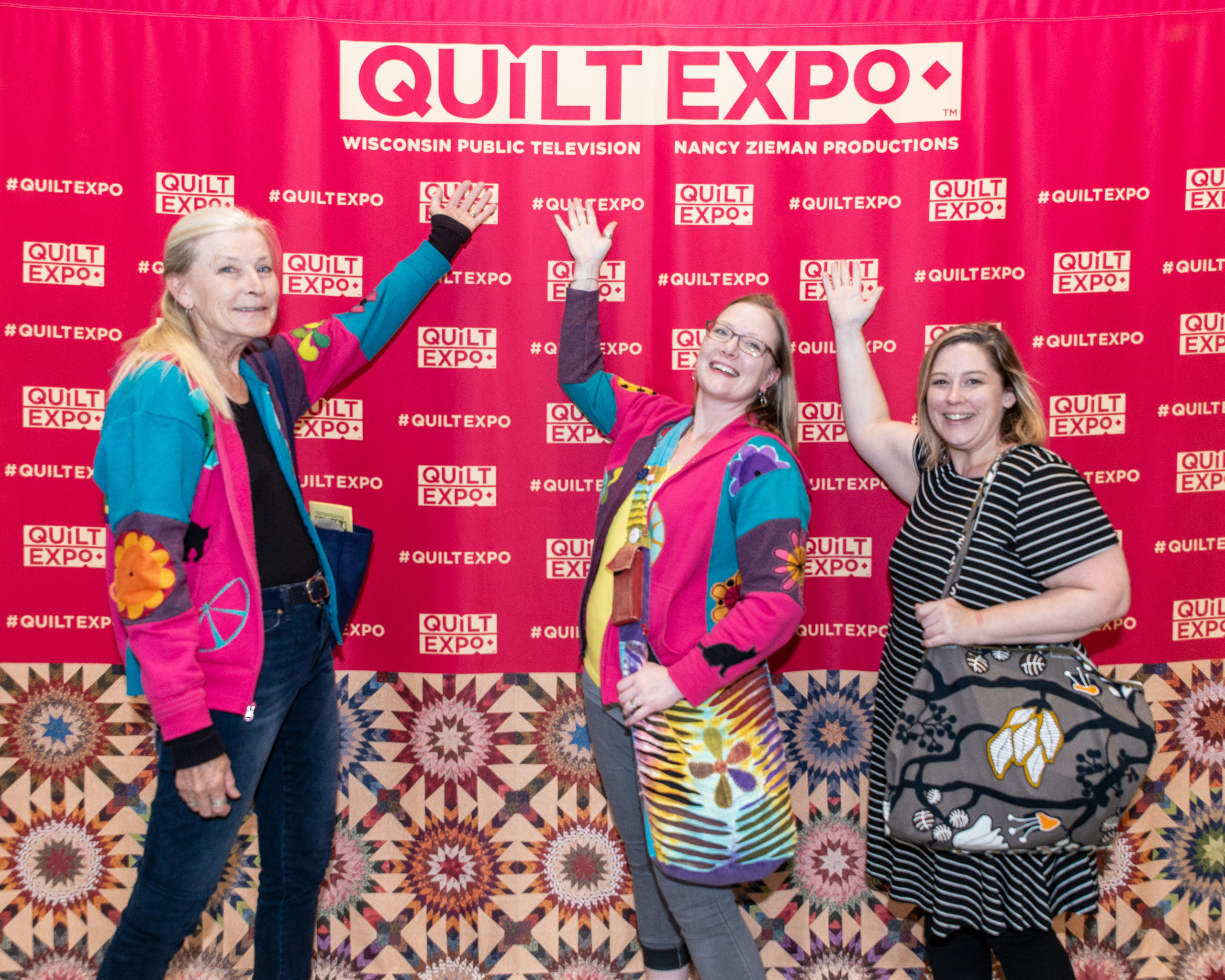 Three attendees pose in front of the photo backdrop at Quilt Expo's entrance.
