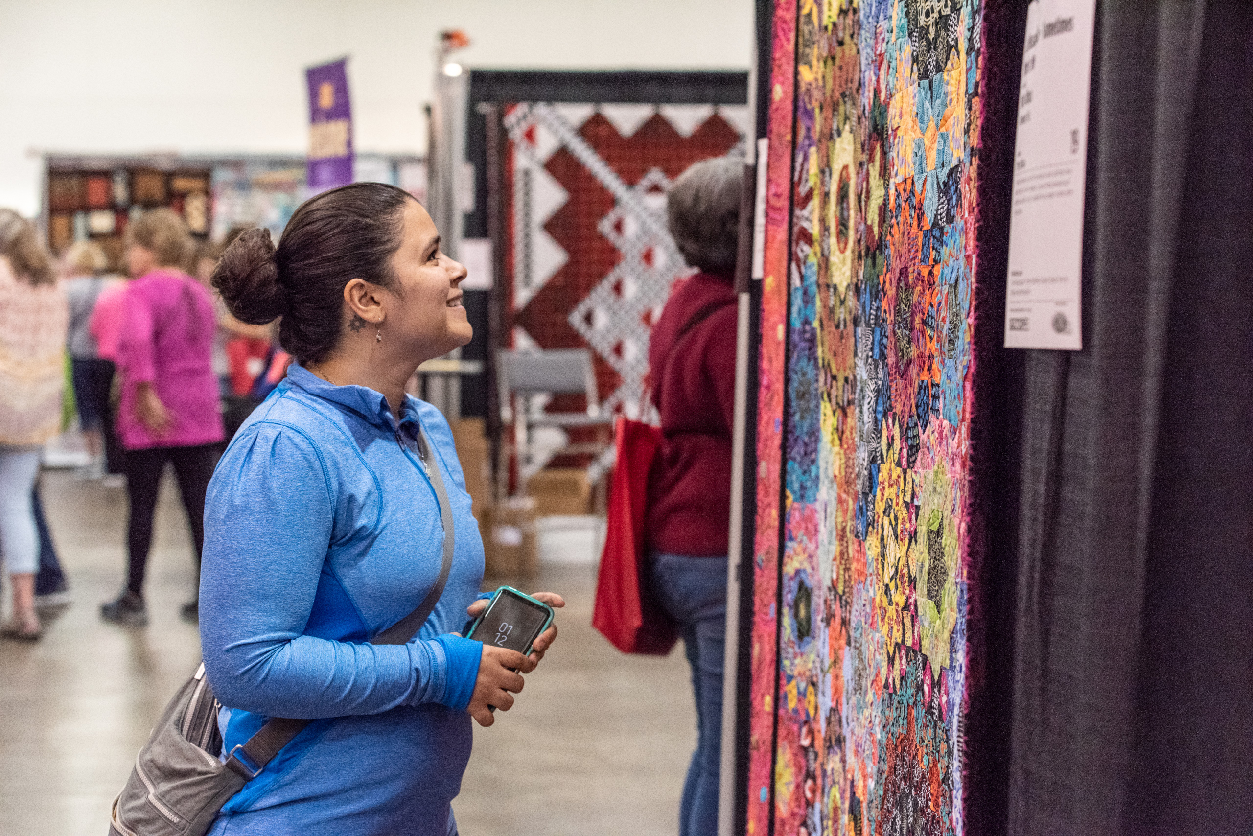 An attendee smiles while admiring a quilt in the Quilt Expo Quilt Exhibit.