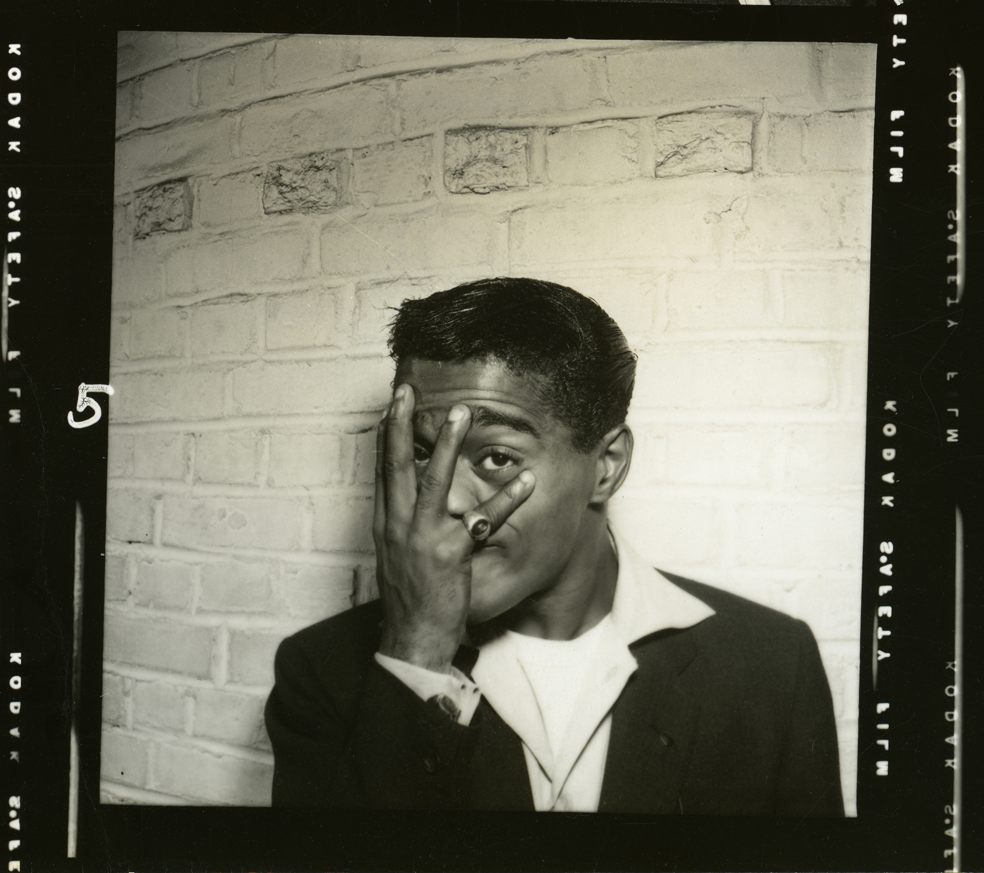 Sammy Davis, Jr. poses with his hand on his face