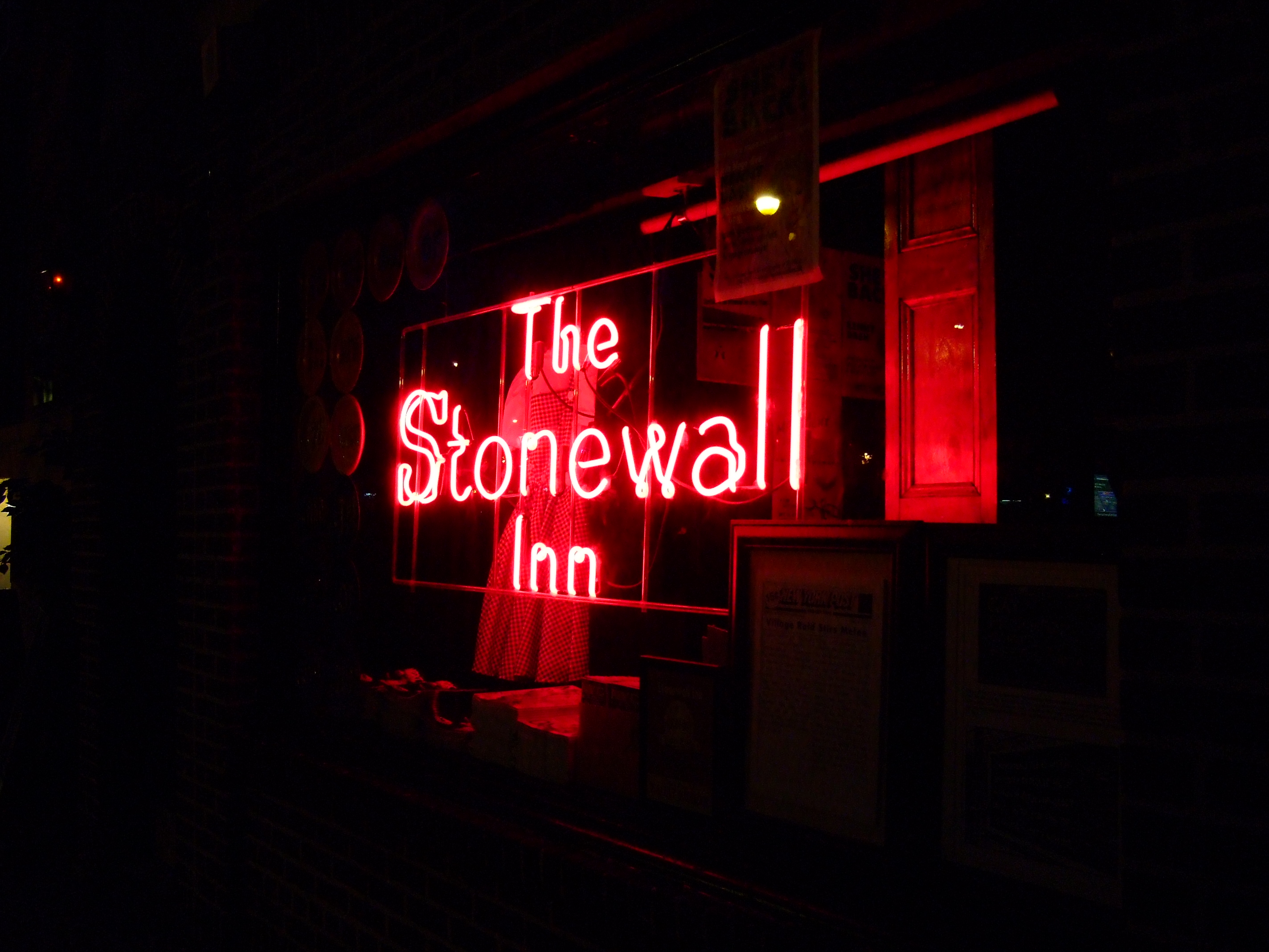 A red neon sign at night reads The Stonewall Inn