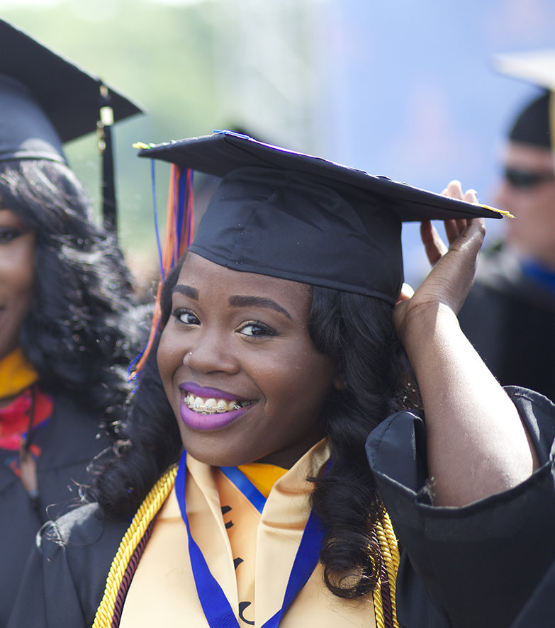 "A female college graduate smiles in a still from ""Tell Them We Are Rising"""