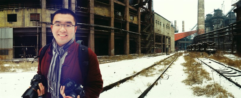 Yinin Wang poses on snowy railroad tracks near abandoned industrial buildings, holding cameras