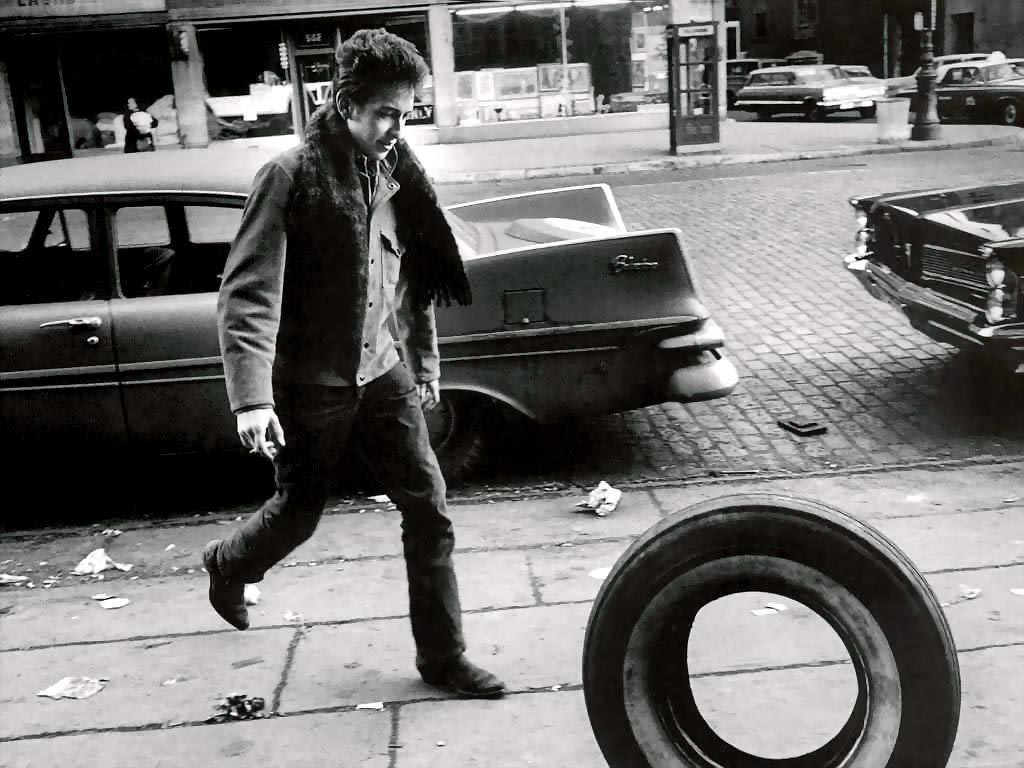 A young Bob Dylan on the street with a tire