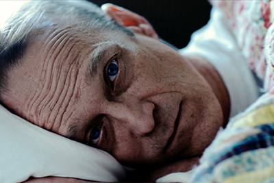 Closeup of an older man's tired face as he lies in bed.