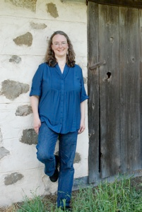 Kathleen Ernst poses by an old cabin