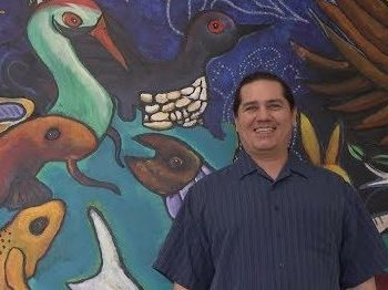 Teacher Reggie Cadotte (Lac Courte Oreilles Band of Lake Superior Chippewa) stands in front of a mural